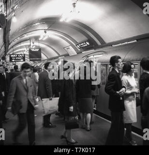 1960s, historical, inside london underground, picture shows a Piccadilly tube train at a platform at a station, on the busy platform people are boarding the train which is going to Uxbridge.... Opened in 1906, the Piccadilly line runs from North London to NorthWest London. - Stock Photo