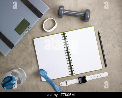 Closeup on laying on the floor weight scales, grey dumbbell, white fitness tracker, bottle of water, tape measure, black pen, opened notebook and smar - Stock Photo