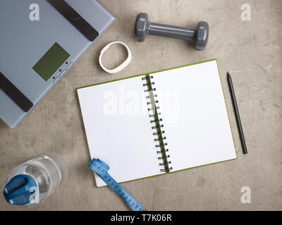 Closeup on laying on the floor weight scales, grey dumbbell, white fitness tracker, bottle of water, tape measure, black pen and opened notebook. - Stock Photo
