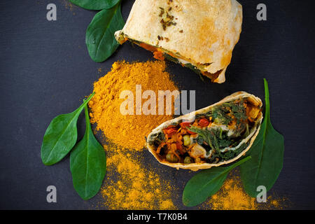 Vegetable savory strudel, with tomatoes and mushrooms on black background - Stock Photo