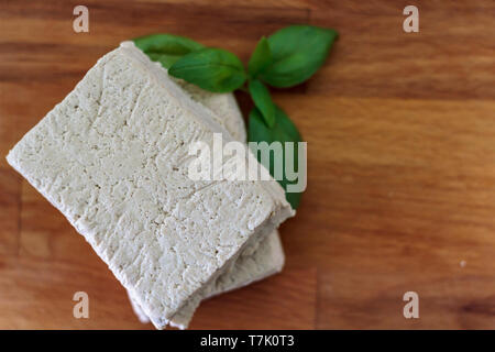 Top view of white tofu on wooden board - Stock Photo