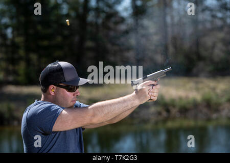 A man shooting a pistol with the ejected shell in the air. - Stock Photo