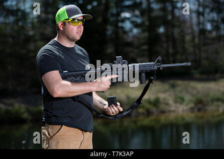 A man holding a modern sporting rifle in one hand and the magazine in the other hand. - Stock Photo