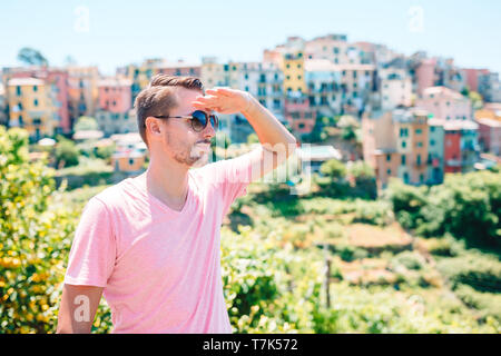 Back view of young man background stunning village. Tourist looking at scenic view of Manarola, Cinque Terre, Liguria, Italy - Stock Photo