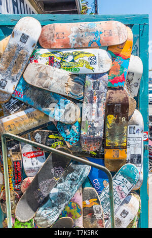 A pile of preowned skateboard decks arranged in a random fashion, some broken and some whole with each having a different design pattern in front of a - Stock Photo