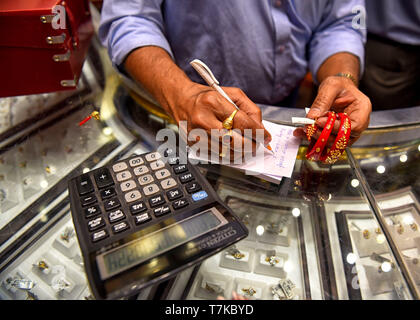 Kolkata, West Bengal, India. 7th May, 2019. A salesman seen calculating the price of golden bangles in a jewelry shop during Akshaya Tritiya festival day at Kolkata. Akshaya Tritiya is a very popular festival among the Hindus and Jains. The most popular activity during the festival is buying gold as it is believed that it will bring good fortune for the buyer, as a result demand of Golden jewelry are higher during this time. Credit: Avishek Das/SOPA Images/ZUMA Wire/Alamy Live News - Stock Photo