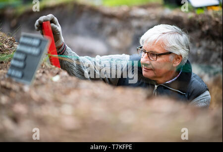 Bielefeld, Germany. 08th May, 2019. Detlev Jaszczurok, excavation technician of the LWL in Münster, misses a site of the excavated Roman marble. Archaeologists of the Landschaftsverband Westfalen-Lippe (LWL) have uncovered the remains of a 2000 year old Roman marsh marsher in the district of Sennestadt. Credit: Guido Kirchner/dpa/Alamy Live News - Stock Photo