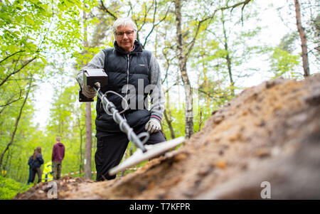 Bielefeld, Germany. 08th May, 2019. Detlev Jaszczurok, excavation technician of the LWL in Münster, Germany, investigates a mound with a metal detector. Archaeologists of the Landschaftsverband Westfalen-Lippe (LWL) have uncovered the remains of a 2000 year old Roman marsh marsher in the district of Sennestadt. Credit: Guido Kirchner/dpa/Alamy Live News - Stock Photo