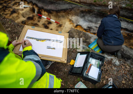 Bielefeld, Germany. 08th May, 2019. A trainee as an excavation technician of the LWL traces on a sheet of paper the uncovered spot of the Roman marble. Archaeologists of the Landschaftsverband Westfalen-Lippe (LWL) have uncovered the remains of a 2000 year old Roman marsh marsher in the district of Sennestadt. Credit: Guido Kirchner/dpa/Alamy Live News - Stock Photo