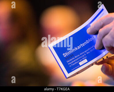 08 May 2019, Hessen, Frankfurt/Main: A shareholder holds up his voting card block in the Jahrhunderthalle during the Annual General Meeting of Deutsche Börse AG. Photo: Andreas Arnold/dpa - Stock Photo