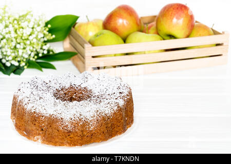 Apple Bundt Cake on white wooden table with apples and spring bouquet. Selected soft focus - Stock Photo