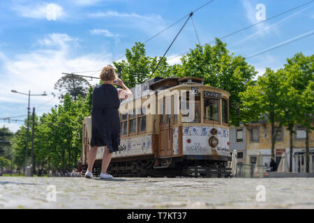 Traditional electric tram in downtown Porto, Portugal with a tourist taking a photograph. - Stock Photo