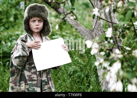 a boy in a camouflage uniform and a hat with earflaps stands in an Apple orchard with a clean white sheet - Stock Photo