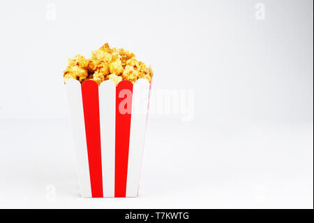 Tasty popcorn delicious in a paper red and white line cup.Horizontal orientation with copy space. - Stock Photo