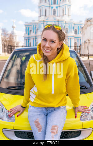 happy woman near yellow car in city in yellow clothes - Stock Photo