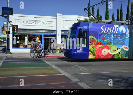 A female cyclist waits at a traffic light alongside a Tucson streetcar covered in sushi ads, in front of Creations and rainbow crosswalk, Tucson, AZ - Stock Photo