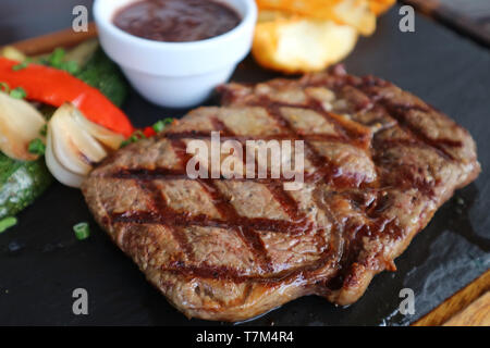Closeup grilled ribeye steak with red wine sauce served on hot stone plate - Stock Photo