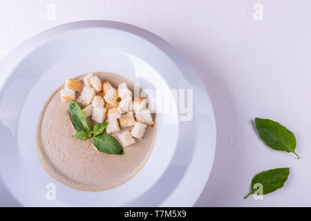 Mushroom cream soup in a white plate and on a white background - Stock Photo
