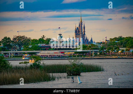 Orlando, Florida. April 02, 2019. Taxi boat and panoramic view of Cinderella's Castle and vintage Train Station at Magic Kingdom in Walt Disney World - Stock Photo