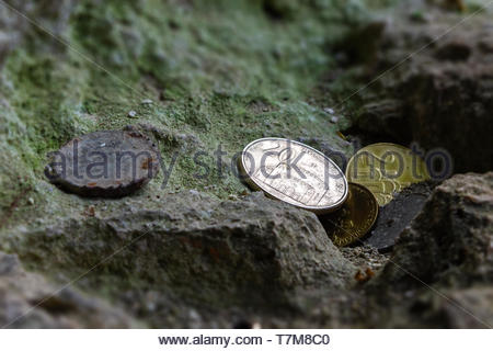 several Serbian, new and old corroded coins were left near a religious object on a moss stone - Stock Photo