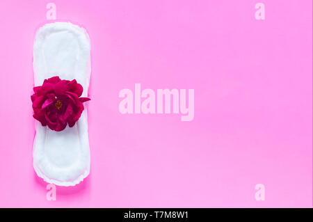 Sanitary napkin with red rose on it. On the bright pink background. Period days concept showing feminine menstrual cycle. - Stock Photo