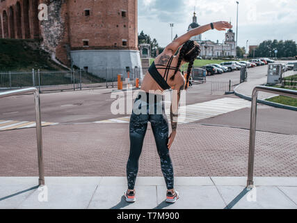 The girl in tattoos, in the summer in city, trains fitness, gymnastics workout. Sportswear leggings top. In the morning before the run. Back view - Stock Photo