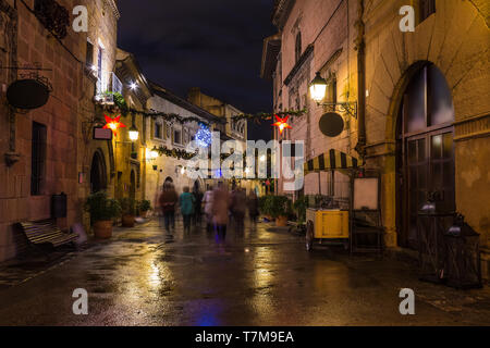 Barcelona, Catalonia, Spain - November 17, 2018: Beautiful night view long-exposure of an illuminated street with motion blurred tourists in the open- - Stock Photo