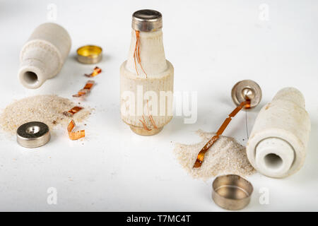 Old ceramic electric fuse. Blown and badly repaired security for energy, Bright background. - Stock Photo