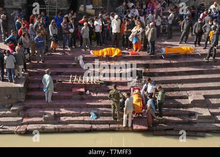 Preparation for cremation of bodies at ghat on Bagmati River, Pashupatinath Hindu temple, Kathmandu, Nepal - Stock Photo