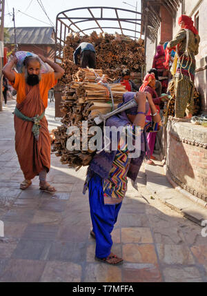 Workers unload firewood from a truck and carry it to the funeral ghats, Pashupatinath Hindu temple, Kathmandu Valley, Nepal - Stock Photo
