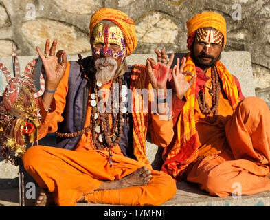 Two sadhus (holy men) with painted faces, clad in orange robes, sit on a bench at Pashupatinath Hindu temple, Kathmandu Valley, Nepal - Stock Photo