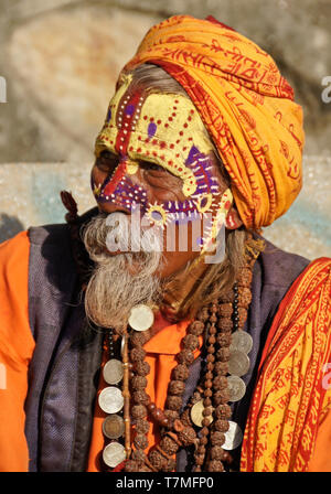 Portrait of a sadhu (holy man) with painted face, clad in orange robes, Pashupatinath Hindu temple, Kathmandu Valley, Nepal - Stock Photo