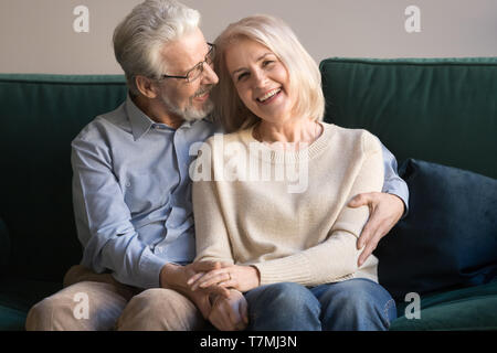 Head shot portrait of aged loving husband embracing smiling wife - Stock Photo