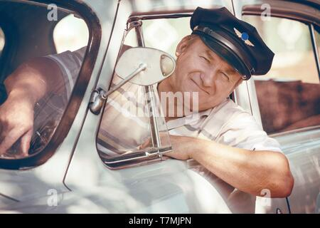taxi driver looks out the window of a retro car - Stock Photo