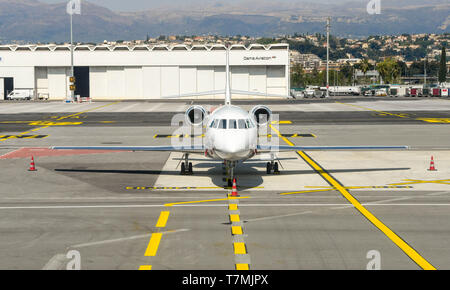 NICE, FRANCE - APRIL 2019: Head on view of a Falcon private executive jet on the ground at Nice Airport in the South of France. - Stock Photo