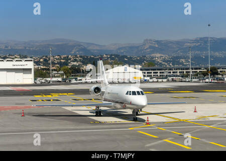NICE, FRANCE - APRIL 2019: Falcon private executive jet on the ground at Nice Airport in the South of France. - Stock Photo