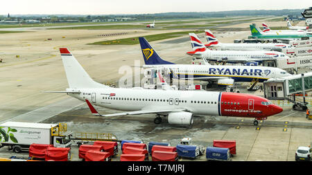 LONDON GATWICK AIRPORT, ENGLAND - APRIL 2019: Boeing 737 operated by Norwegian and other jets lined up at London Gatwick Airport - Stock Photo