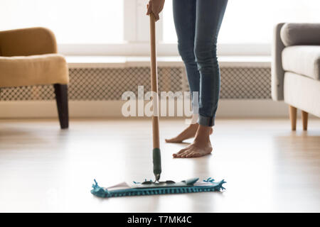 Closeup image barefoot girl doing house cleaning using wet mop - Stock Photo