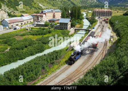 Switzerland, Canton of Valais, Gletsch, The Rhone, the railway station and the steam train, the hotel Glacier du Rhône and the Blue House in the background - Stock Photo