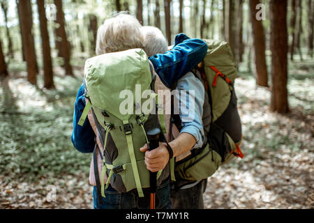 Lovely senior couple hugging in the forest while hiking with backpacks, back view