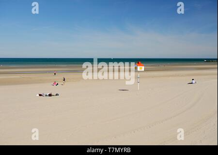 France, Nord, Dunkerque, Malo-les-Bains, vacationers on the sand next to a pole topped with a house - Stock Photo
