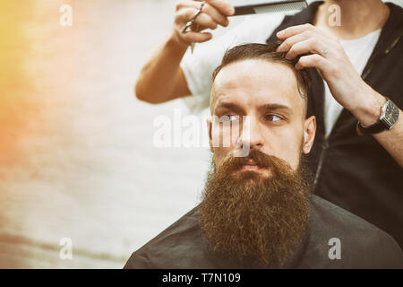 Master cuts hair and beard of men in the barbershop, hairdresser makes hairstyle for a young man - Stock Photo