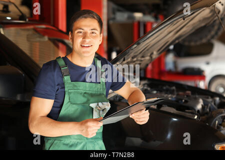 Young auto mechanic with clipboard near car in service center - Stock Photo