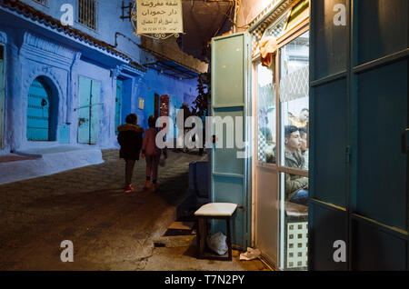 Chefchaouen, Morocco : People walk past an illuminate barber shop at night in the blue-washed alleyways of the medina old town. - Stock Photo