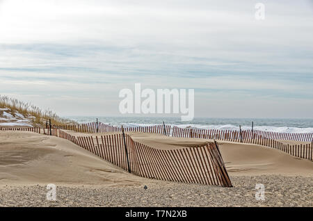 Snow fences losing their red paint in the battle with the elements on Lake Michigan - Stock Photo