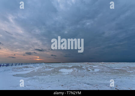 Frozen foreground leads to water and a sunset on Lake Michigan at Ludington's North Breakwater Light at Stearns Park - Stock Photo