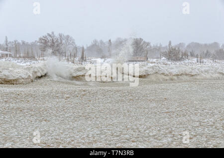 Water from Lake Michigan splashing against ice on the shore with thousands of chunks of ice in the lake - Stock Photo