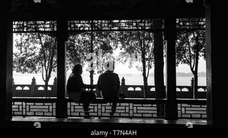 A black and white silhouette of 2 people by the park, Beijing, China. Stock Photo