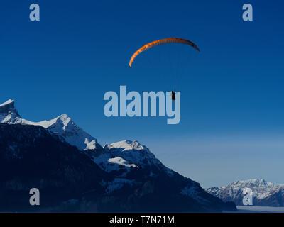 A paraglider high above the Swiss Alps near Hasliberg Meiringen - Stock Photo