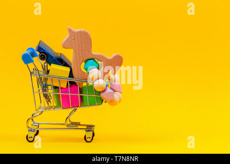 Shopping cart or supermarket trolley full of colorful numbers on yellow background - Stock Photo